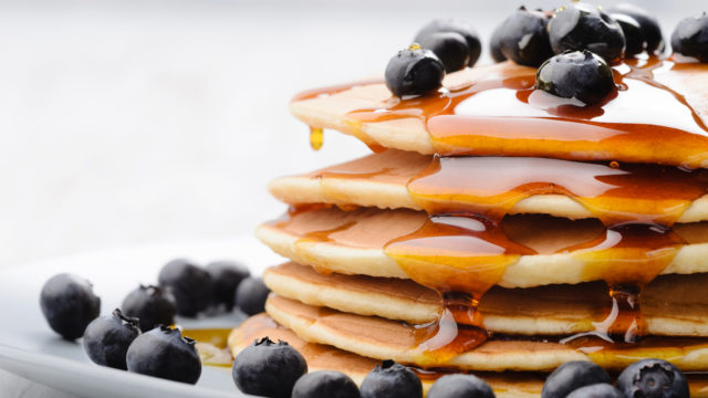 Delicious pancakes close up, with fresh blueberries and maple sy