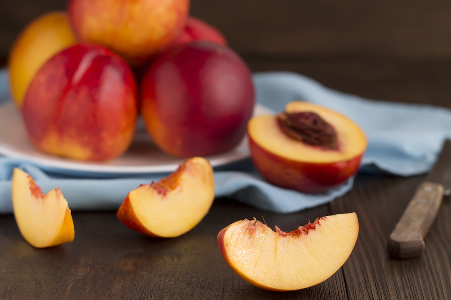 Slice Of Nectarine And Whole Fruits On A Wooden Table.