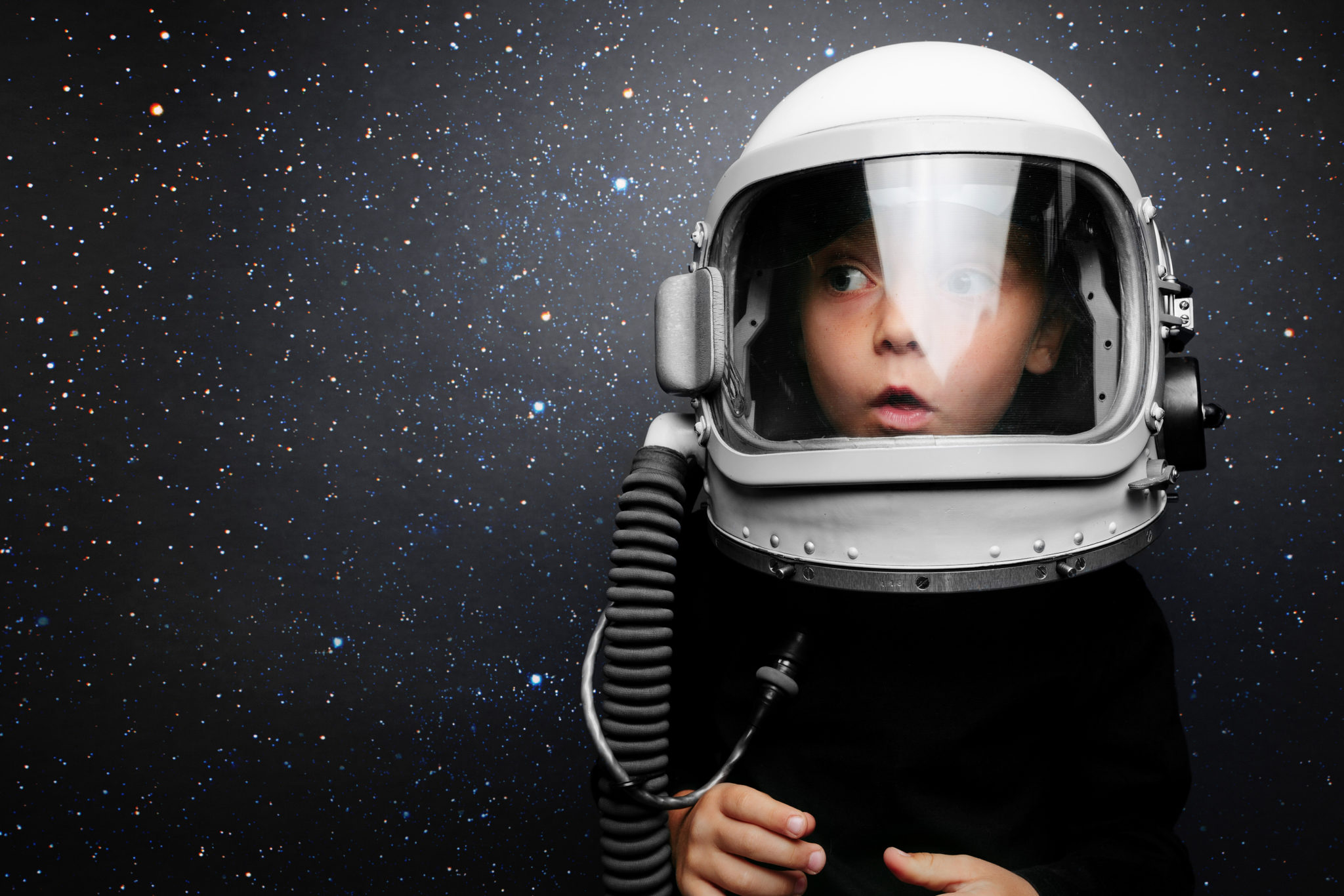 A small child imagines himself to be an astronaut in an astronau