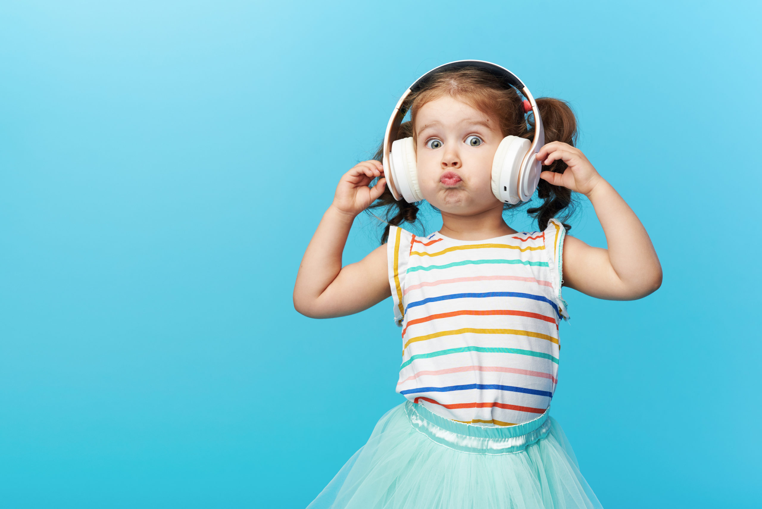 Happy Smiling Child Enjoys Listens To Music In Headphones Over C