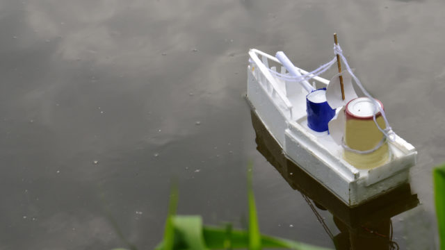 A Children's Boat Floats In A Pond, Next To Green Reeds.