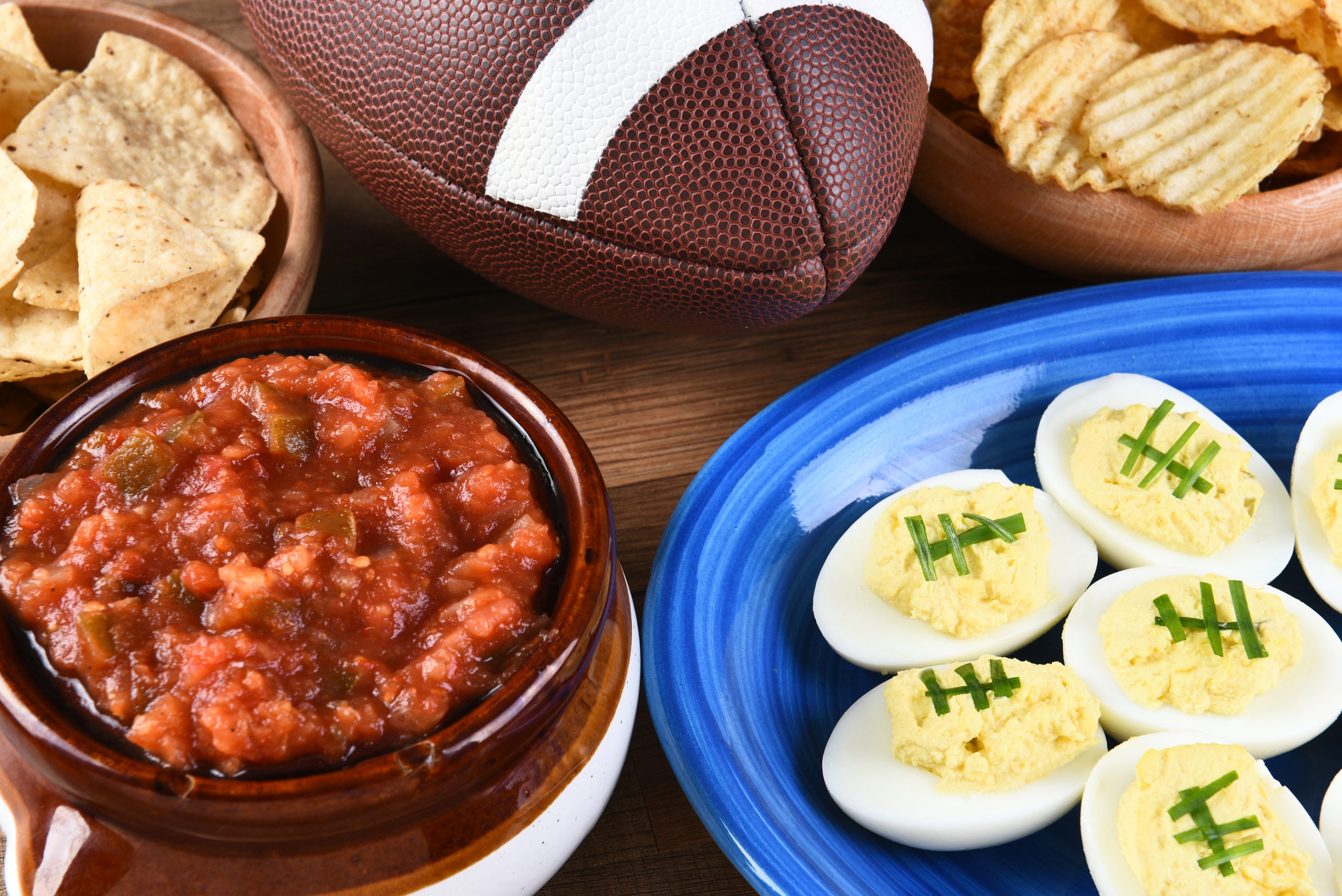 Closeup of snacks for watching a football game, chips, salsa and
