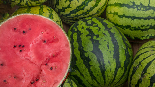 Many Big Sweet Green Watermelons And One Cut Watermelon.young Gr